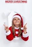 Lycklig santa flicka på jul som uppåt pekar för att kopiera utrymme Arkivbild