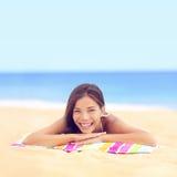 Lycklig semesterkvinna som solbadar att koppla av på stranden Arkivfoto