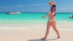 Lycklig sexig kvinna i bikini som tycker om det tropiska havet och den exotiska stranden i Punta Cana, Dominikanska republiken lager videofilmer
