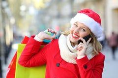 Lycklig shoppare med shoppingpåsar som kallar på telefonen i jul Fotografering för Bildbyråer