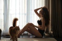 Lycklig sinnlig kvinna i damunderkläder som spelar med den hemmastadda katten Royaltyfri Fotografi