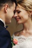 Lycklig sinnlig stilig brudgum och blond härlig brud i vit Royaltyfri Bild