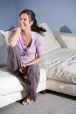 lycklig sittande le kvinna för soffa arkivbild