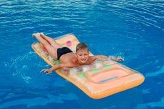 Lycklig sju-år-gammal pojke som ligger på en luftmadrass i den utomhus- pölen i sommaren bl?tt vatten arkivbild