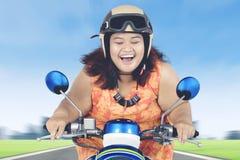 Lycklig sjukligt fet kvinna som rider en sparkcykel Arkivbilder