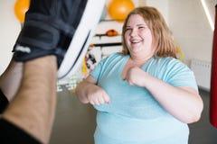 Lycklig sjukligt fet kvinna som utarbetar fotografering för bildbyråer