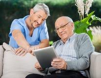 Lycklig sjuksköterska Helping Senior Man, i att använda minnestavlan arkivbild