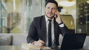 Lycklig skäggig affärsman i svart sammanträde för affärsdräkt på tabellen som ler och talar på mobiltelefonen i modernt stock video