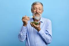 Lycklig skäggig man som äter sallad, hälsovård royaltyfria bilder