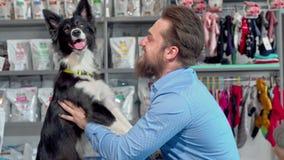 Lycklig skäggig man som spelar med hans hund på det veterinär- kontoret lager videofilmer