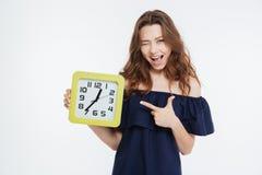 Lycklig skämtsam ung kvinna som blinkar och pekar på klockan Royaltyfri Bild