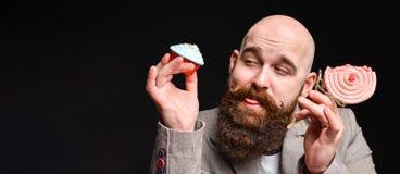 Lycklig sk?ggig skallig man som rymmer tv? kr?m- kakor p? svart bakgrund royaltyfri foto