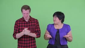 Lycklig skandinavisk hipsterman som ger upp tummar med den överviktiga asiatiska kvinnan som ser förvirrad stock video