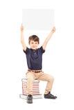 Lycklig skolapojke som rymmer en tom panel ovanför hans huvud som placeras på Arkivfoton
