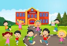 Lycklig skolbarntecknad film framme av skolan Arkivbild