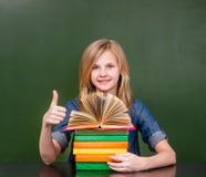 Lycklig skolflicka i klassrumvisningtumme upp royaltyfria foton