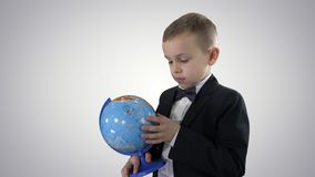 Lycklig skolpojke i en formell dräkt som studerar ett jordklot på lutningbakgrund stock video