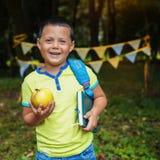 Lycklig skolpojke med en ryggsäck och en bok fyrkant Begreppet är royaltyfri fotografi