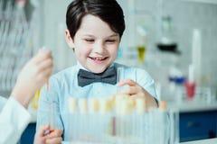 Lycklig skolpojke med flaskor i kemisk labb Royaltyfri Bild