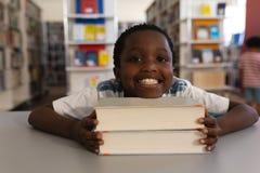 Lycklig skolpojke som lutar hans framsida på böcker och ser kameran på tabellen royaltyfria bilder