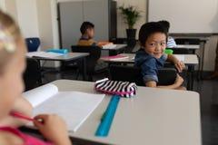 Lycklig skolpojke som tillbaka ser i klassrum arkivbild