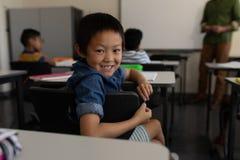 Lycklig skolpojke som tillbaka ser i klassrum fotografering för bildbyråer