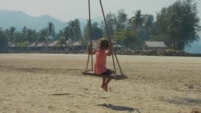 Lycklig skratta barnflicka som svänger på den tropiska sandiga stranden med roliga sinnesrörelser stock video