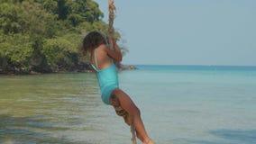 Lycklig skratta barnflicka som svänger på den tropiska sandiga stranden med roliga sinnesrörelser lager videofilmer