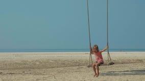 Lycklig skratta barnflicka som svänger på den tropiska sandiga stranden med roliga sinnesrörelser arkivfilmer