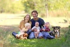Lycklig skratta familj av 5 personer och hund i Sunny Garden arkivbild