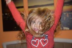 Lycklig skratta hoppa liten flicka på sängen arkivbilder