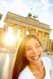 Lycklig skratta kvinna på den Brandenburg porten, Berlin Arkivfoton