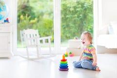 Lycklig skratta litet barnflicka som spelar i vitt rum Arkivbilder