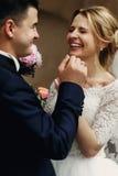 Lycklig skratta stilig brudgum och ursnygg emotionell brud i wh Arkivfoto