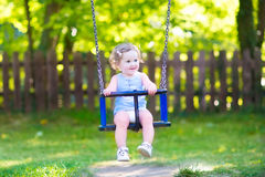 Lycklig skratta svängande ritt för litet barnflicka på lekplats Royaltyfri Fotografi