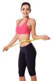 Lycklig slank kvinna som mäter henne midja arkivfoto