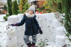 lycklig slott för snö för ungeflickabyggnad på vinterferier arkivbilder