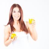 Lycklig smilling med hållande exponeringsglas för tandkvinna av orange fruktsaft och apelsinen i händer Sund livsstil Arkivfoton