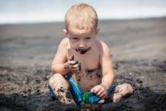 Lycklig smutsig barnlek med sand på familjstrandsemester Royaltyfri Bild