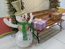 Lycklig snögubbe och färgrika gåvor på bänk Royaltyfria Bilder