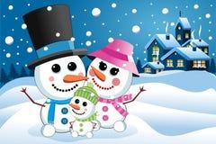 Lycklig snögubbefamilj under snöfall Arkivbild