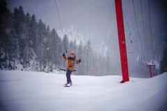 Lycklig snowboarder som vinkar hans armar på alpint lutningen Ryssland för skida royaltyfria bilder