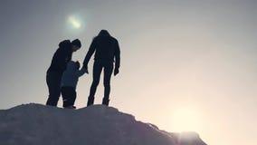 lycklig solnedgång för familj Fadern, modern och den lilla sonen har gyckel, och spela på snöig vinter gå i natur lager videofilmer