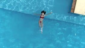 Lycklig sommarferie som flyger surret över härlig flicka i baddräkt, simmar i blått vatten arkivfilmer