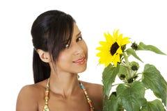 Lycklig sommarflickastående med solrosen Arkivbild