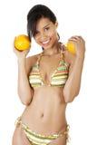 Lycklig sommarkvinna i bikini med apelsiner. Arkivbild