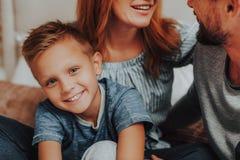 Lycklig son som sitter på säng samman med föräldrar arkivfoton