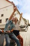Lycklig sparkcykel för barnparridning i stad Lopp för stilig grabb och för ung kvinna Affärsföretag- och semesterbegrepp arkivfoton