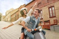 Lycklig sparkcykel för barnparridning i stad Lopp för stilig grabb och för ung kvinna Affärsföretag- och semesterbegrepp Royaltyfria Bilder