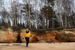 Lycklig sport- och modevänentusiast som utarbetar på en strand som bär den ljusa gula tröjan och svarta handskar och ett lock royaltyfri foto